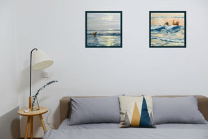 Two framed paintings of dogs on a beach by Hannah Phelps shown hung in a bedroom