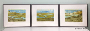 Three framed woodblock prints of a New England beach by artist Hannah Phelps.
