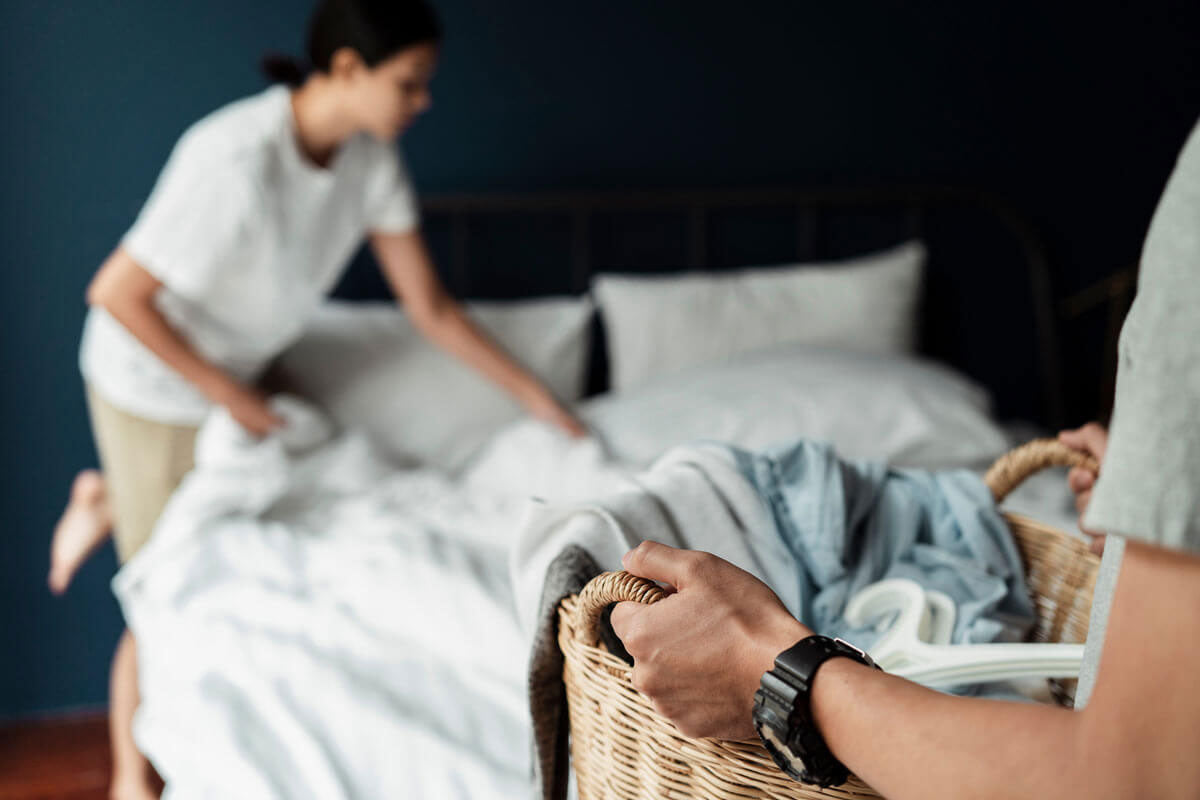 woman making bed and man holding folded laundry in basket