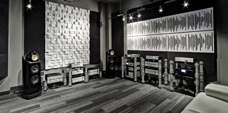 Black and white picture of Bowers & Wilkins speakers next to acoustic panels