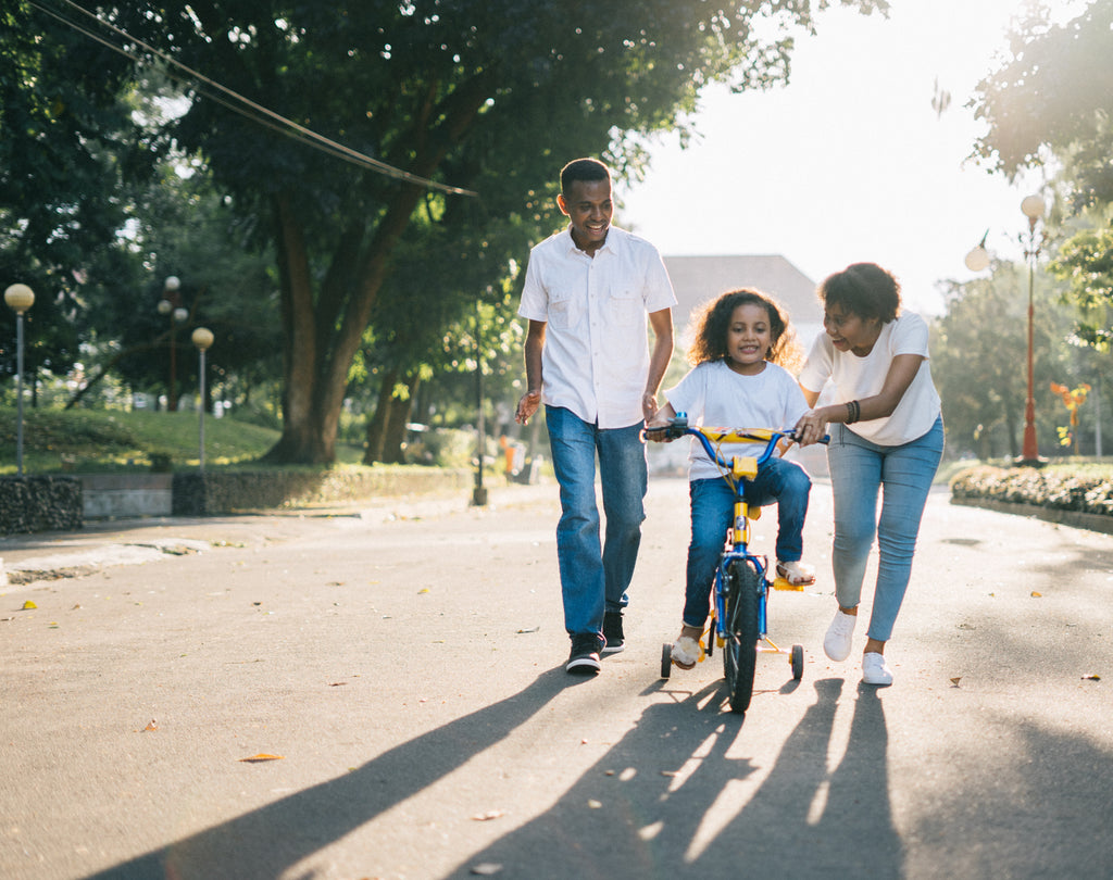 Parents helping happy child ride a bike