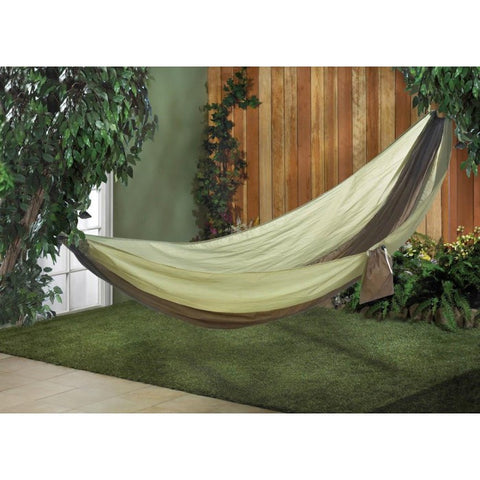 Green parachute camping hammock in an outdoor environment.