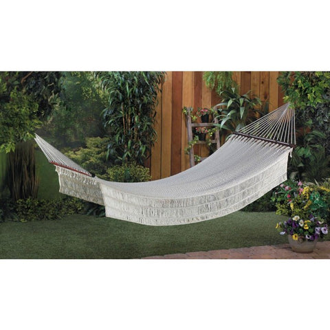 A white rope hammock in an outdoor setting.