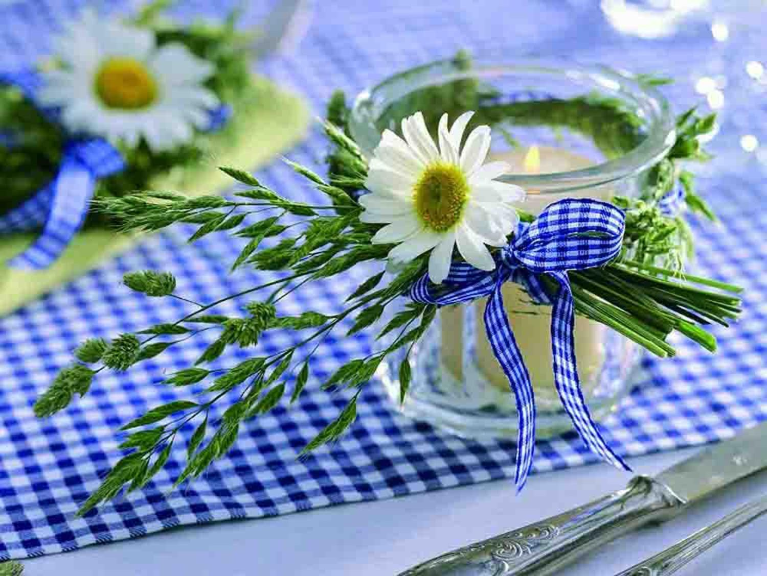 Yellow and white daisy inside of a glass jar with a tealight candle inside on top of a blue and white checkered table cloth.