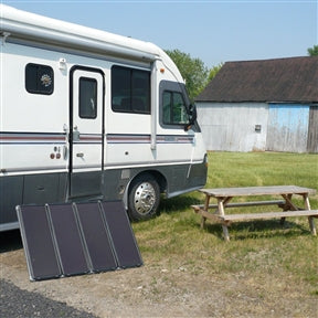 The solar system in front of an RV. This 60-Watt Solar Panel Charging Kit with Charge Controller & Inverter gives you several more reasons to love the sun. It provides the power you need, while helping you save money and protect the environment. This kit is ideal for cabins, recreational vehicles, remote power, back-up power, and 12-volt battery charging. It comes with everything you need to start producing up to 60 Watts/4 Amps of clean, free power in all weather conditions.