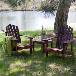Outdoor adirondack chairs and a matching table by a lake.