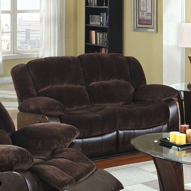 Brown recliner love seat in a living room setting. Enjoy the comfort and Simply casual style of this love seat with built-in recliner. Plush seats and arms offer comfort, while enliven the beauty of your decor. Made of quality fabric and leatherette in brown finish, adding to its grace. Includes one love seat only.