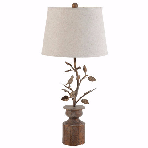 Light brown lamp with round base and branches leading to the bulb area with birds in the branches.  A round white lampshade.