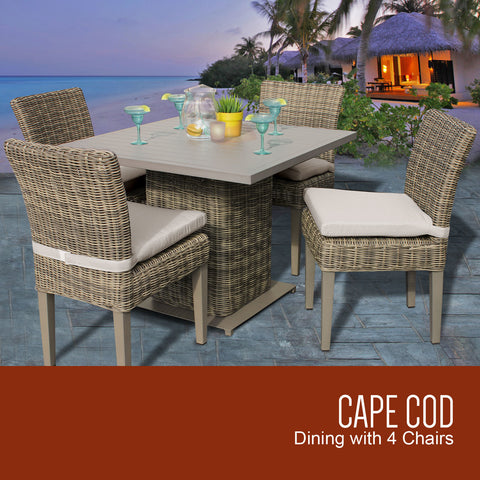 4 cape cod wicker chairs with table by an ocean setting with  a lighted hut nearby.
