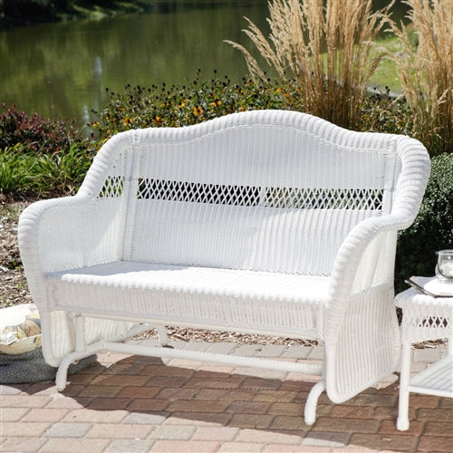 White wicker glider loveseat in an outdoor setting.