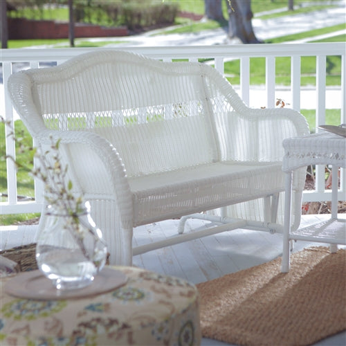white wicker glider loveseat right facing view on a front porch.