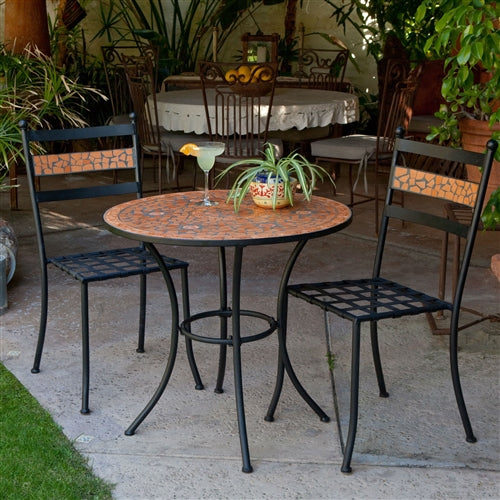 black and orange terracotta table with 2 chairs in an outdoor setting.