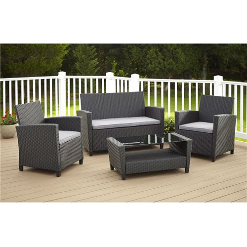 Gray wicker 4 piece pation set with gray cushions on an outdoor patio.