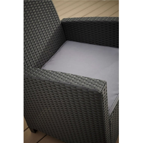 Highlight of a wicker armchair with a gray cushion.
