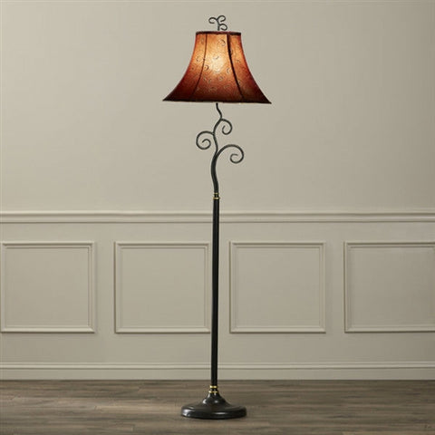 A floor lamp against a white wall with the lamp on and the buld glowing.