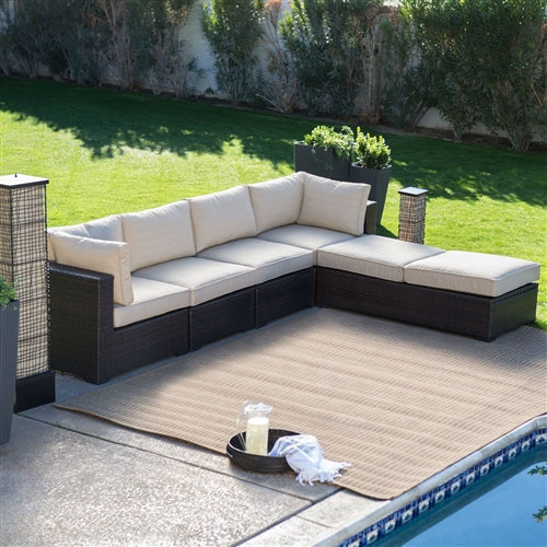6 Piece brown wicker patio sectional set with beige seat covers.