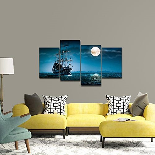living room scene yellow sectional sofa with blue painting in the background of a ship in the moonlight.