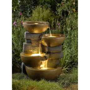 Brown lighted bowls stacked on each other with water flowing between the bowls.