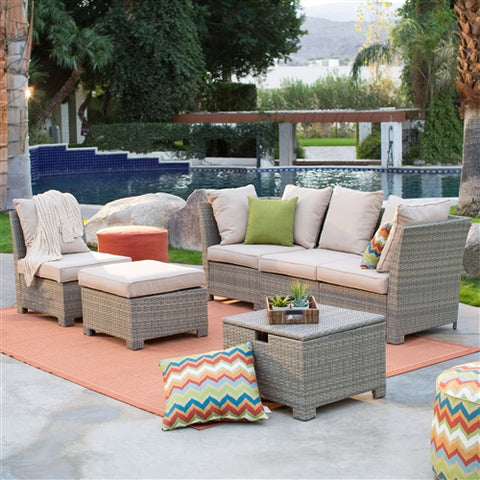 Beautiful light gray wicker patio set with light cushions in front of a swiming pool.