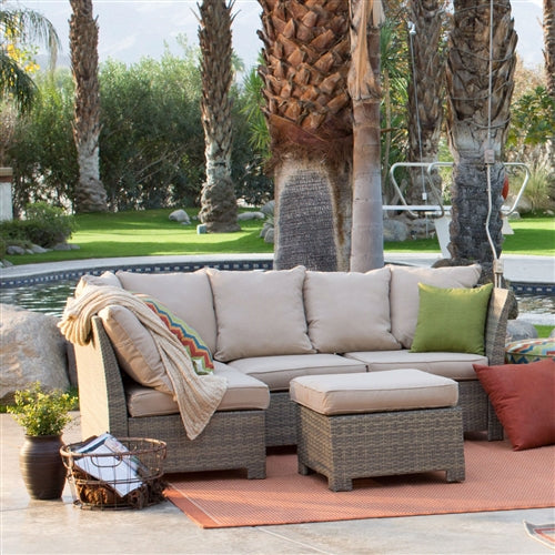 Palm trees are in the background of this wicker patio set with couch and armless chair and ottoman.