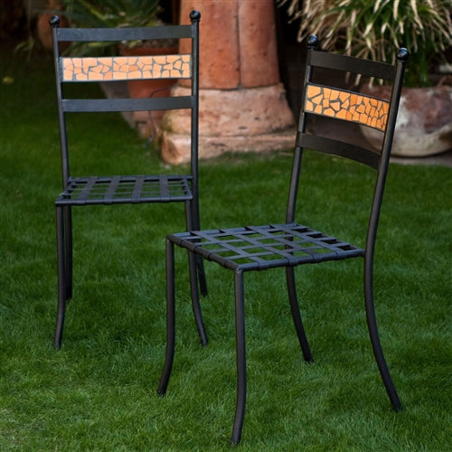 2 black chairs with an orange terracotta tile back in an outdoor setting.