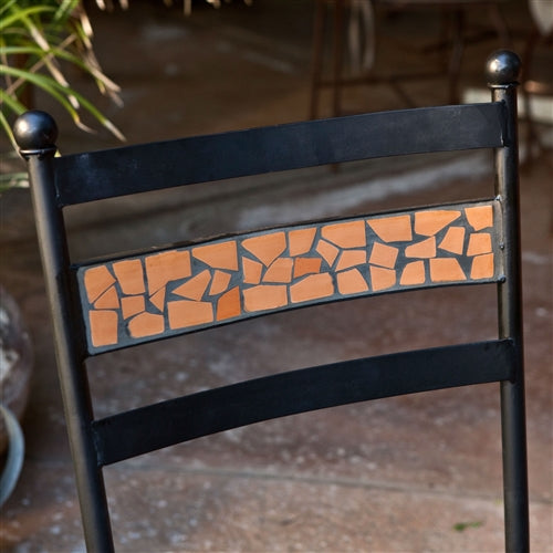 terracotta tile detail in the back of a black chair.