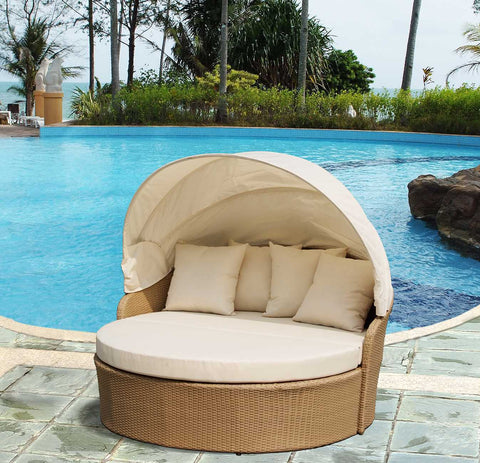 Round beige and wicker outdoor bed with canopy by a pool.