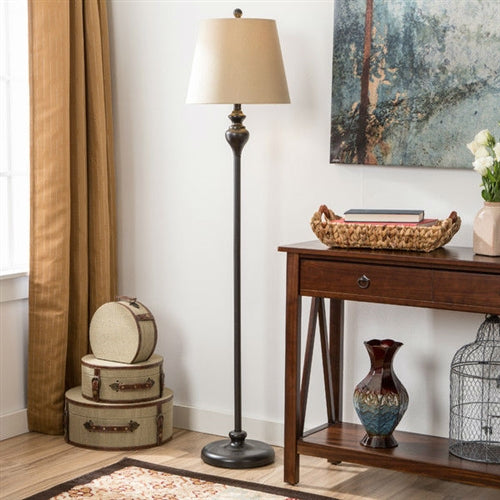 A floor lamp next to a table surrounded by various home decor products.