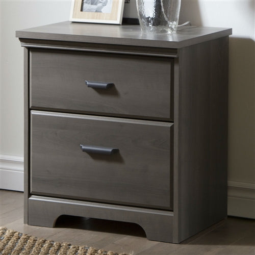 Photo of the nightstand in a real setting. You will Simply love this 2-Drawer Bedroom Nightstand in Gray Maple Wood Finish for its many storage spaces! It has a rich finish that creates an air of sophistication in any bedroom enhances it.