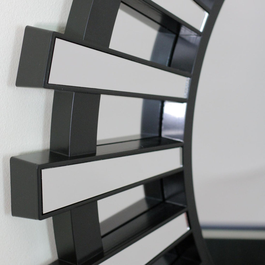 Zoomed in detail of the mirror construction. This beautifully crafted mirror will add a touch of modern elegance to any room in your home Features a round black frame with mini mirrored columns inspired by a shimmering sunburst ! Can be hung vertically or horizontally Includes hanging hardware.