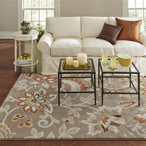"Photo of the rug in an actual setting. Warm up any room with the orange and yellow accents of this 5'2"" x 7'2"" Tufted Cotton Area Rug Neutral Beige Yellow Orange Floral Pattern. Flowing florals are set against a neutral backdrop to create a stylish scene for your entryway, living room, or dining room. Woven from cotton, this rug is soft and offers fuss-free maintenance."