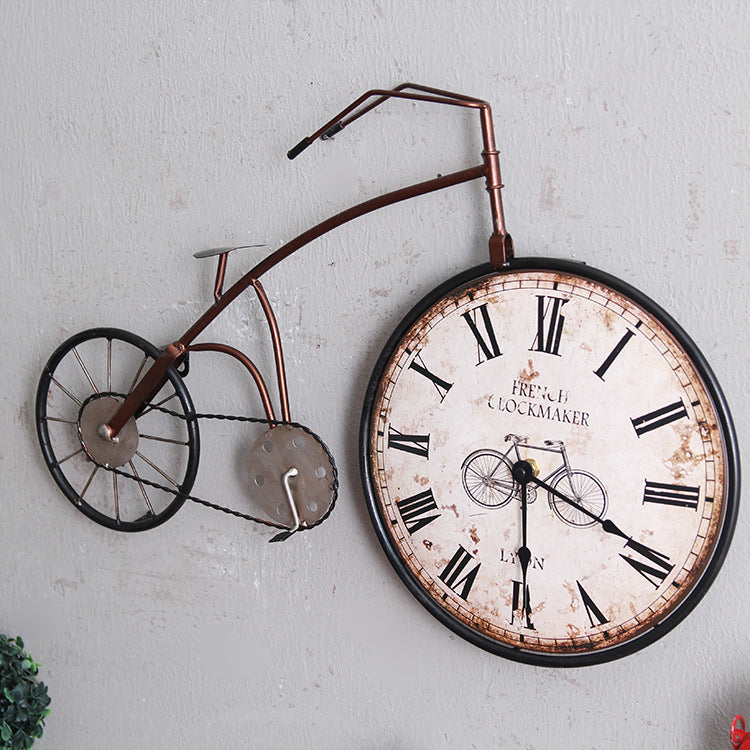 red oldstyle bicycle wall clock with clock in the front wheel diagonal view.