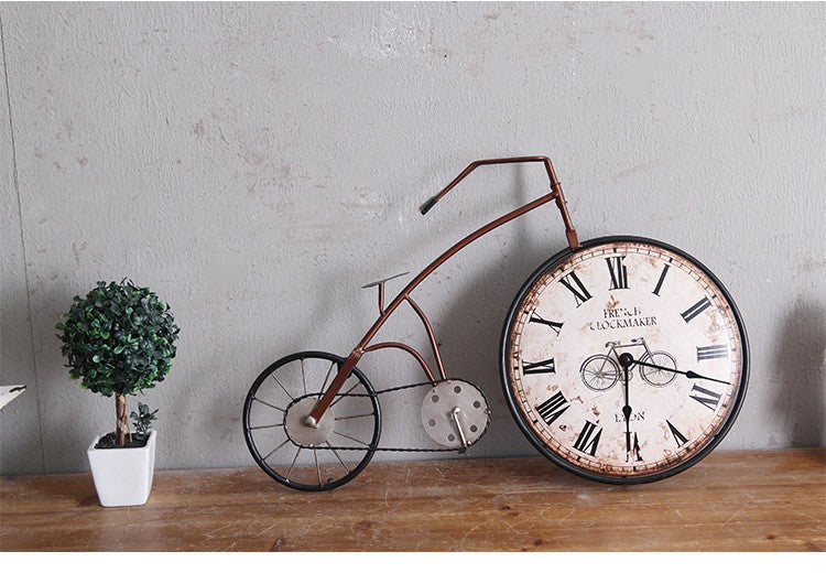 red oldstyle bicycle wall clock with clock in the front wheel sitting on a table.