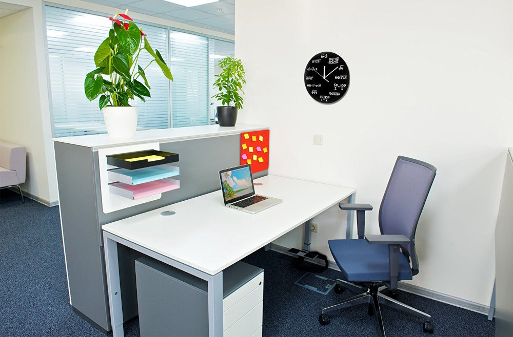 Blace wall clock on the wall in an office environment