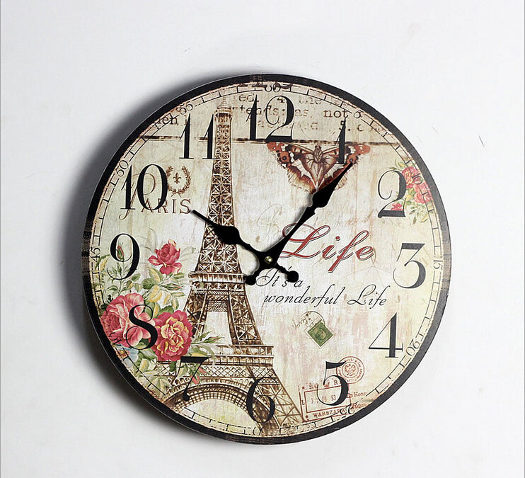tan wall clock with pink flower and the eiffel tower.
