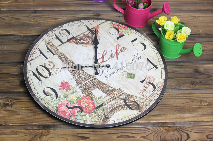 tan wall clock with pink flower and the eiffel tower lying on a table for size appreciation.