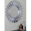 Photo of the mirror in an actual setting. This beautifully crafted mirror will add a touch of modern elegance to any room in your home Features a round silver frame with mini mirrored columns inspired by a shimmering sunburst ! Can be hung vertically or horizontally Includes hanging hardware.
