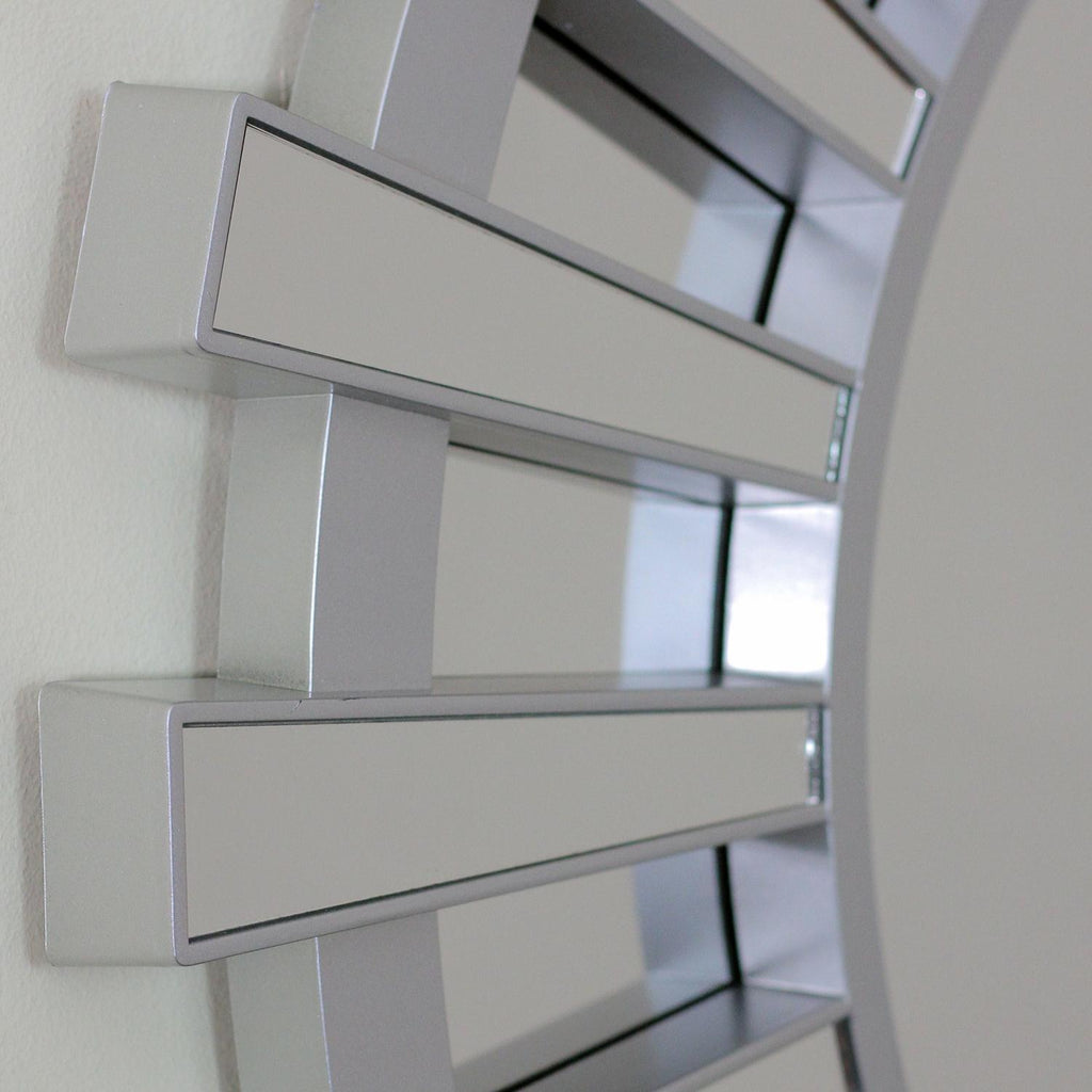 Photo of mirror construction detail. This beautifully crafted mirror will add a touch of modern elegance to any room in your home Features a round silver frame with mini mirrored columns inspired by a shimmering sunburst ! Can be hung vertically or horizontally Includes hanging hardware.