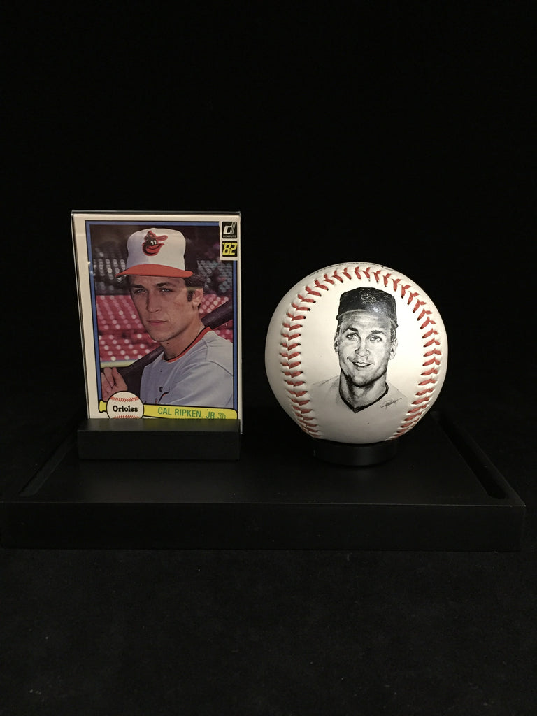 Cal Ripken, Jr 1982 Donruss #405 Rookie Card and Baseball in mint condition. This card come with a commemorative ball with a picture of Cal Ripken Jr. on it in a case with clear cover.The card is a head shot of Cal Ripken Jr. wearing a hat and gray jersey holding a bat.