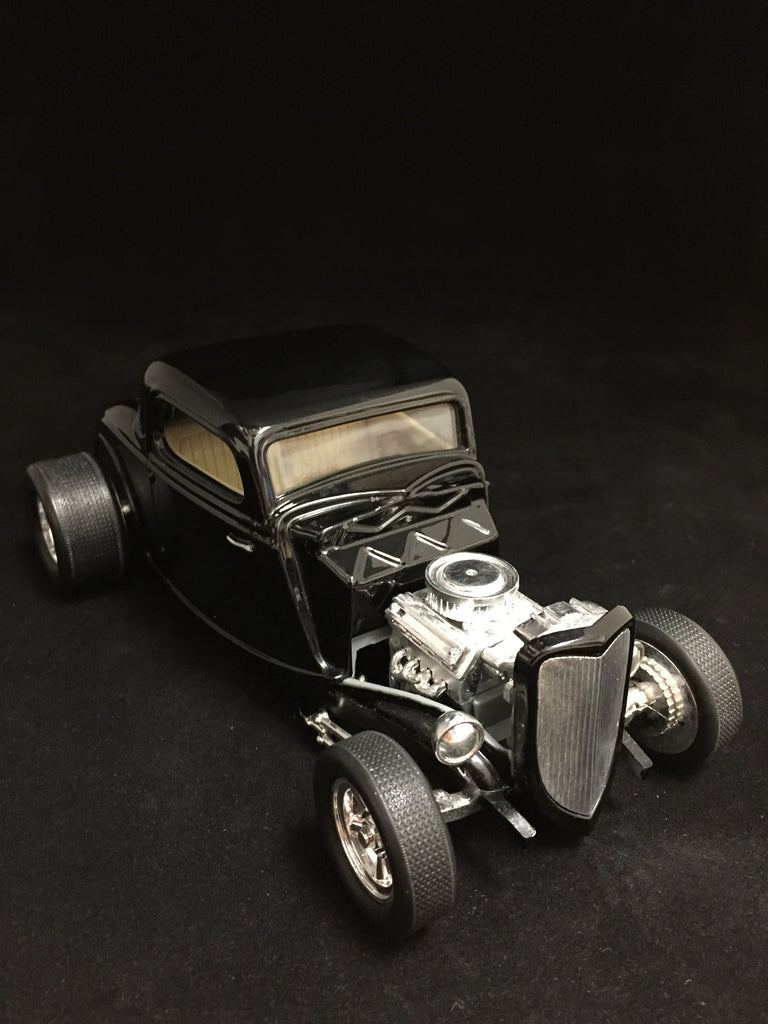 You are looking at a 1:24 scale 1933 Ford racing hot rod made by Racing Champions. Body color is black with light tan interior. Detailed open engine. Body has no blemishes or scratches. Tires spin perfectly.