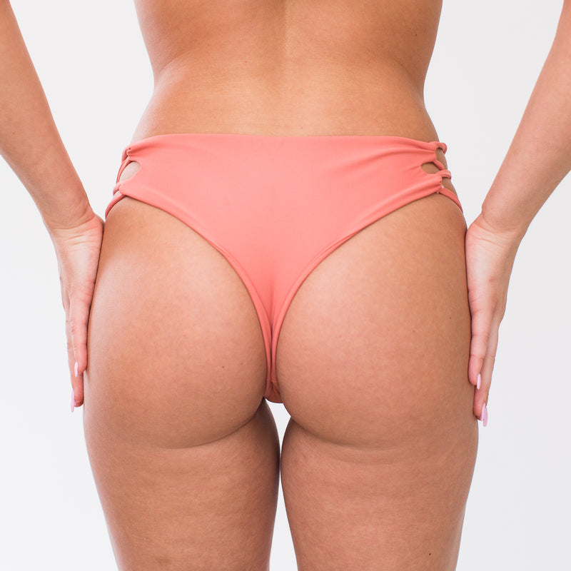 Back of blush swim bottoms made with recycled plastics