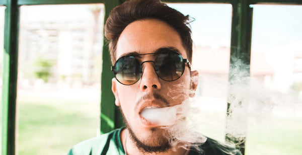 Man with sunglasses vaping the best disposable vape device