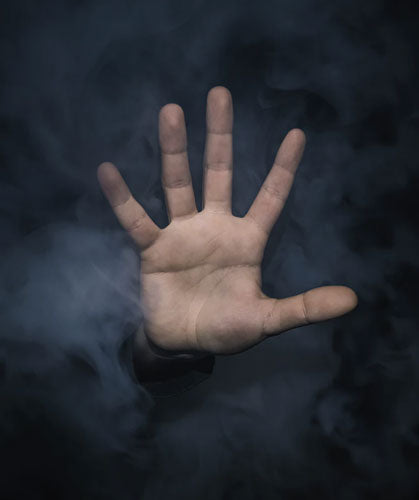 "A left hand palm reaching out in a ""stop"" position with smoke in the background."