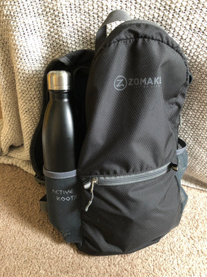 Black water bottle sitting in the outside pouch of a backpack.