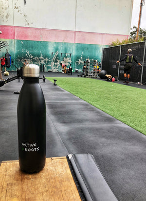 Active Roots water bottle at an outdoor gym space.