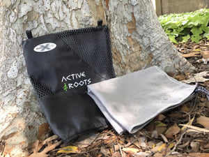 Active Roots microfiber towel laying on leaves leaning against a tree.
