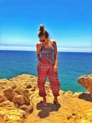 A girl poses in her red stripe harem pants in front of the ocean.