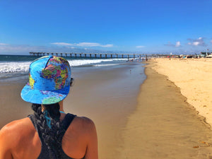A girl looks out along the beach in her world map hat.