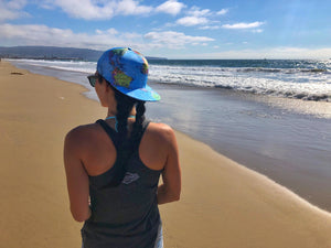 A traveler enjoying her time on the beach in her world map hat.