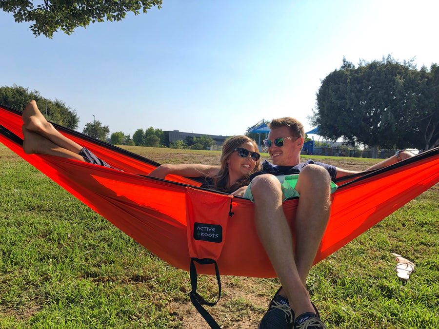 A newlywed couple cuddle together in their orange portable hammock